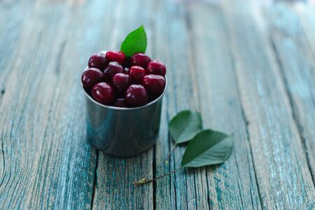 Cherries in a steel mug on a wooden background. Archivio Fotografico - 149050727