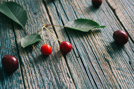 Fresh homemade ripe cherries on a wooden old background. Summer still life. Stock Photo