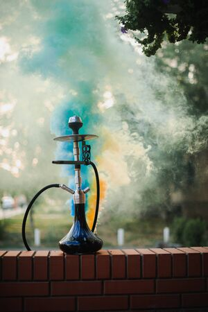 Hookah outdoors on a background of colored smoke. Stock Photo