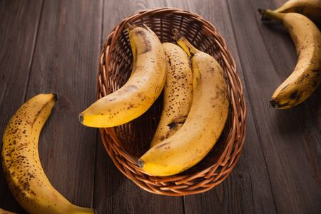Bananas in a basket on a wooden brown natural background. Archivio Fotografico - 149592249