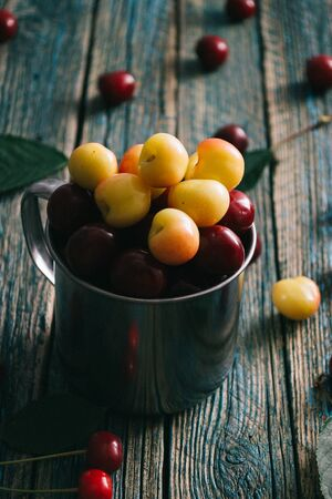 Sweet cherries in a steel mug on an old wooden background. Stock Photo