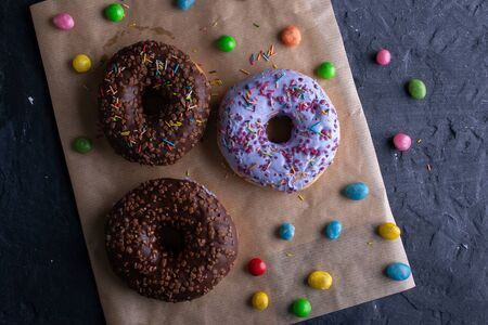 Donuts on a wooden board on a blue concrete background. Archivio Fotografico - 149213716