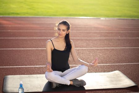 Girl athlete is engaged in meditation at the stadium.