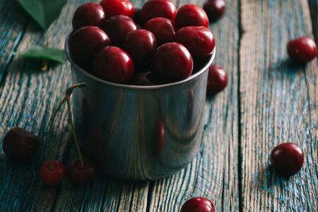 Cherries in a steel mug on a wooden background. Archivio Fotografico - 149215826