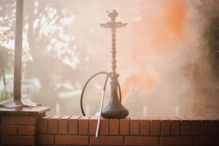 Hookah outdoors on a background of colored smoke. Archivio Fotografico