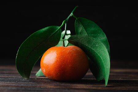 Fresh tangerines with leaves on a wooden old background. Stock Photo