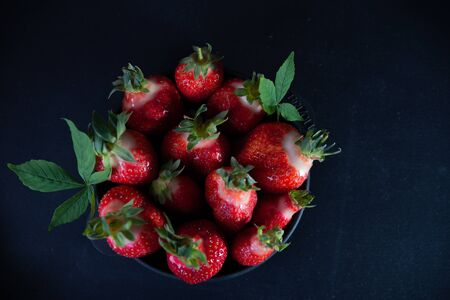 Fresh juicy strawberries in a black plate on a black matte background. Archivio Fotografico