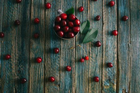 Cherries in a steel mug on a wooden background. Archivio Fotografico - 149215648