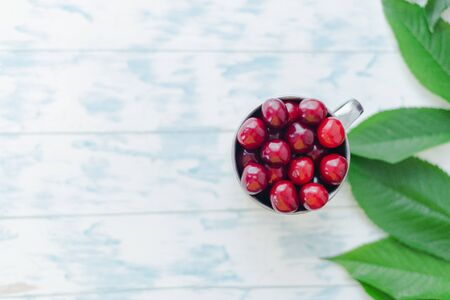 Cherries in a steel mug on a wooden background.