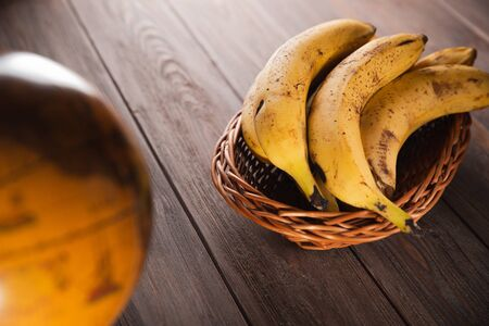 Bananas in a basket on a wooden brown natural background near a brown globe.