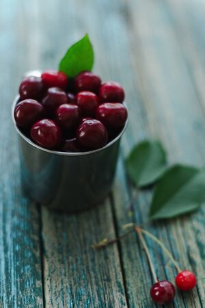 Cherries in a steel mug on a wooden background. Archivio Fotografico - 149215936