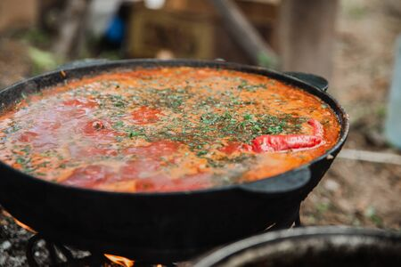 Cooking borsch in the fresh air on a fire in nature. Archivio Fotografico