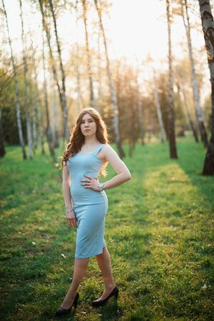 Beautiful young girl in a blue dress in a spring park. Stock Photo