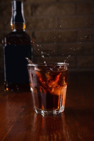 Glass with ice splash of cognac in a bar on a blurred background. Archivio Fotografico - 149592265