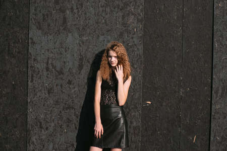 Red-haired girl in a black dress near a dark textured wall.