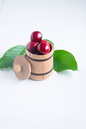 Sweet cherry berries in a wooden small barrel on a white background isolate. Stock Photo