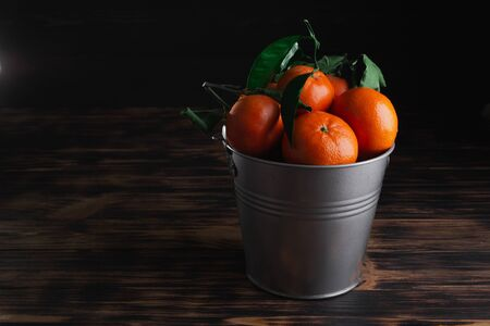 Fresh tangerines with leaves in a bucket on a wooden old background.