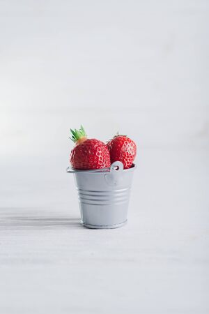 Juicy fresh Strawberries in a small iron bucket on a white wooden background.