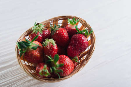 Juicy fresh strawberries in a basket on a white wooden background.