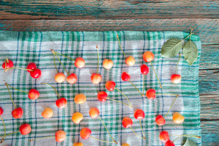 Fresh homemade ripe sweet cherries on squared fabric background. Summer still life.