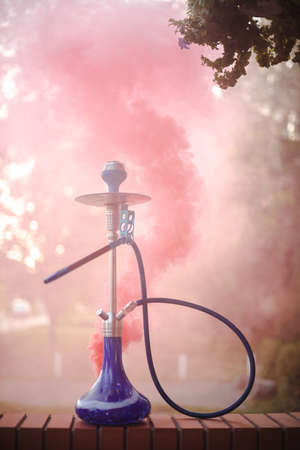 Hookah outdoors on a background of colored smoke. Banque d'images