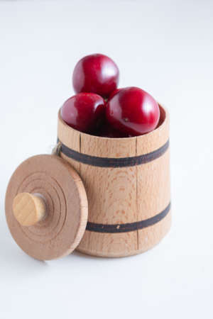 Sweet cherry berries in a wooden small barrel on a white background isolate. Banque d'images