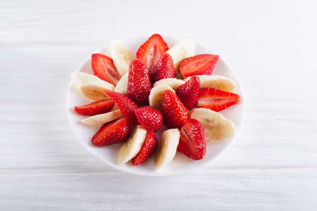 Juicy fresh sliced strawberries with banana on a white plate on a white wooden background.