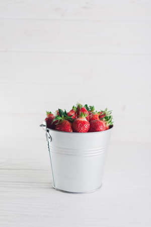 Juicy fresh strawberries in a metal bucket on a white background.