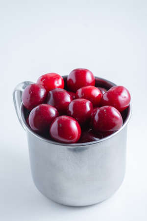 Sweet cherries in a steel mug on a white paper background.