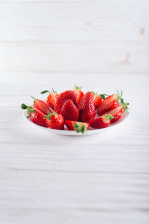 Juicy fresh sliced strawberries on a white plate on a white wooden background.
