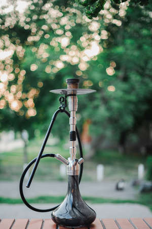 Metal hookah on a summer terrace with a blurred background.