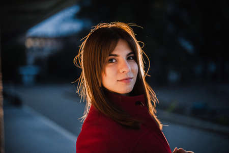 Young beautiful girl in a red coat and hat in the evening in the city. Archivio Fotografico