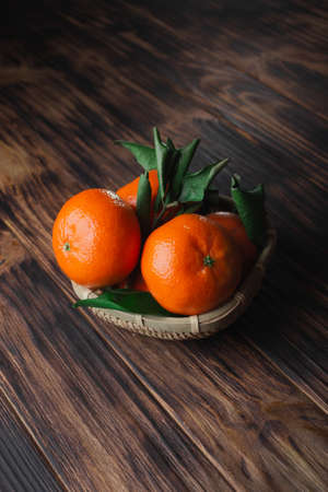 Fresh tangerines with leaves on a wooden old background. Banque d'images