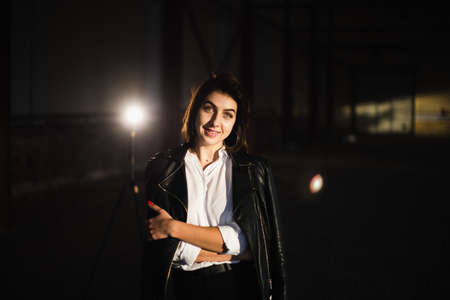 Girl in a leather jacket on an old abandoned construction site. Banque d'images