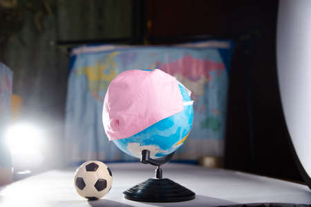 Globe in a medical mask with a soccer ball. The concept of canceling football matches due to coronavirus. Banque d'images