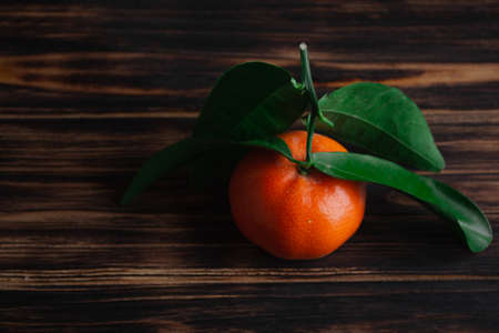 Fresh tangerines with leaves on a wooden old background. Archivio Fotografico