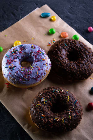 Donuts on a wooden board on a blue concrete background.