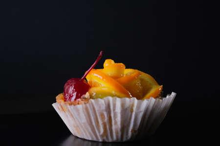 Cheese dessert with orange on a black background.