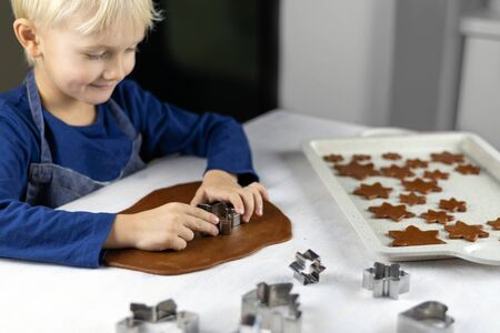 A child cuts gingerbread cookie in the kitchen with a cookie cutter. Little cute moms assistant. Cozy homemade pastries.