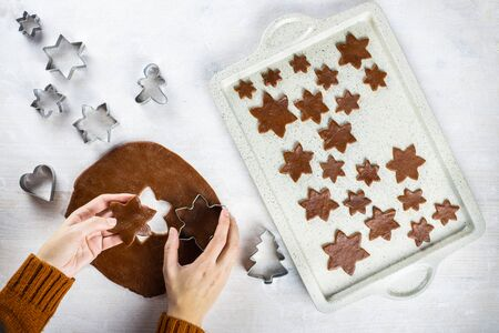 A womens hands cuts a gingerbread cookie with a cookie cutter a snowflakes on a white background. Flat lay cooking.