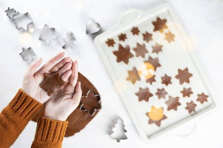 A womens hands hold a gingerbread a snowflakes cookie on a white background. Flat lay cooking.