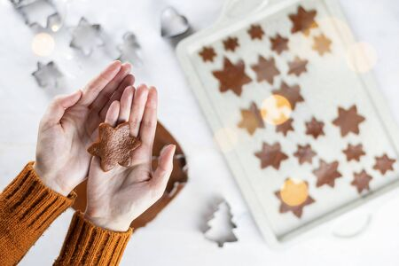 A womens hands hold a gingerbread a snowflakes cookie on a white background. Flat lay cooking. Stock fotó
