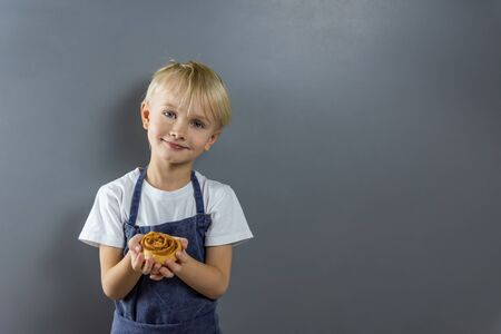 A cute blond-haired boy in a chefs apron holds a Cinnabon bun in his hands. On the right, where the gaze is directed, there is a copyspace.