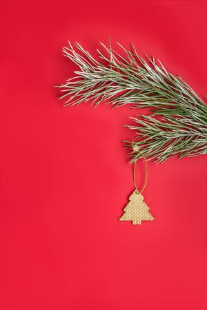 A Christmas toy - a wooden homemade in the form of a fir hanging on a pine branch with hoarfrost. Flat lay on red background.