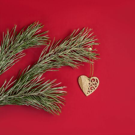 A Christmas toy - a wooden homemade in the form of a heart hanging on a pine branch with hoarfrost. Flat lay on red background. 写真素材