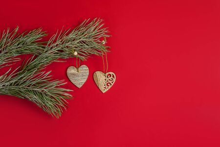 A Christmas toy - a wooden homemade in the form of a heart hanging on a pine branch with hoarfrost. Flat lay on red background.