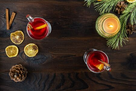 Two glass cups with mulled wine, with slices of orange and a stick of cinnamon, and burning candle in a jar are on a wooden brown table. Flat lay on a dark background with copy space in the center. Banque d'images
