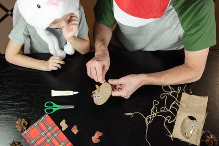 Son and father do the craft together. A boy in a white bunny hat, and dad in a Christmas hat. Hats show a festive mood. Joint family holiday.