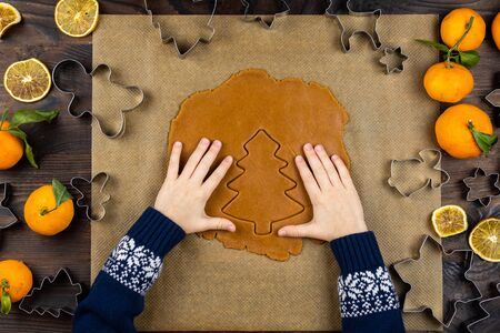 A child hands cuts a gingerbread with a cookie cutter form a fir on a dark wooden background. Little moms assistant. Christmas flat lay.