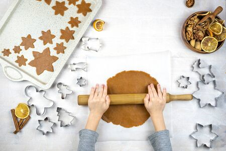 Childrens hands roll out the dough with a rolling pin for cookies, with a cookie cutters on a white background. Little cute moms assistant. Flat lay cooking.